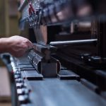 right side close-up of a worker holding a metal plate against a manufacturing machinery, in the right hand, and several other metal plates in his left hand